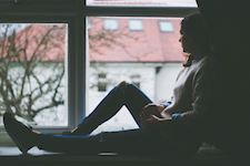 Lady sitting by a window looking out